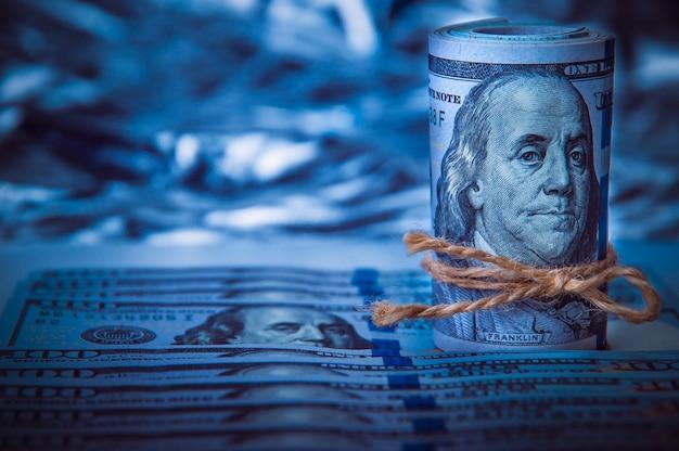 Um rolo dos dólares no fundo de cem notas de dólar dispersadas na luz azul.
