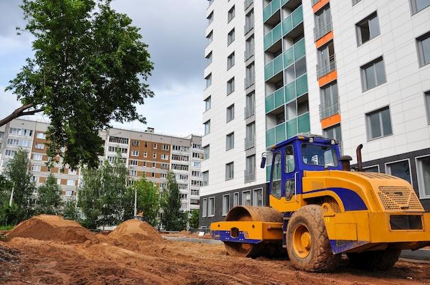 Um rolo trator compacta o terreno para a construção de uma nova estrada na casa de verão