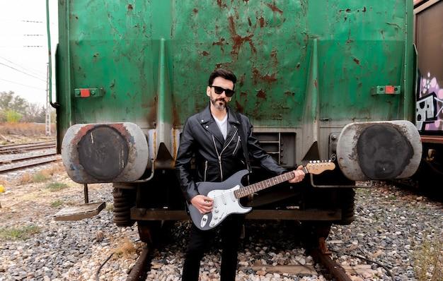 Um roqueiro com óculos escuros e sua guitarra posando entre vagões de trem abandonados.