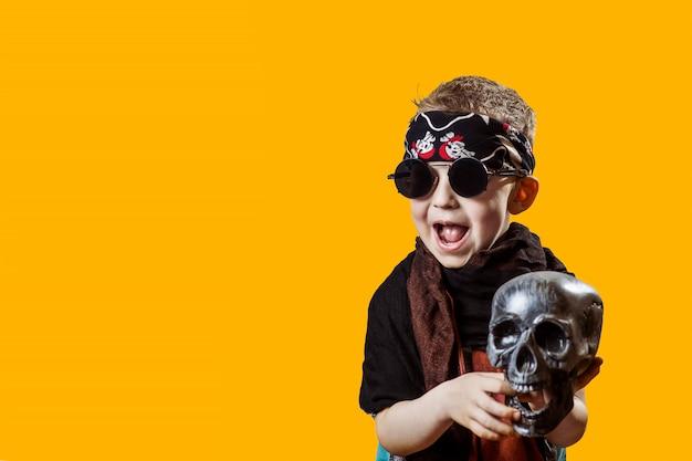 Um roqueiro de menino de óculos escuros, cachecol, bandana e com uma caveira nas mãos sobre um fundo brilhante