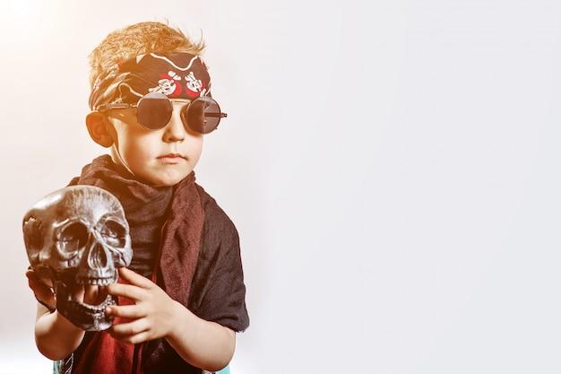 Um roqueiro de menino de óculos escuros, cachecol, bandana e com uma caveira nas mãos