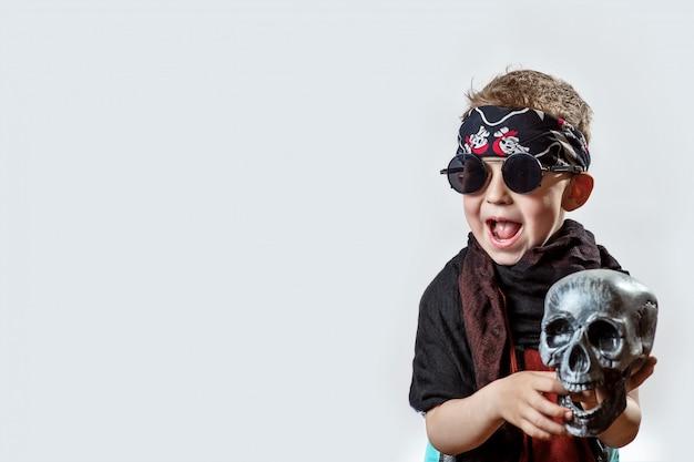 Um roqueiro de menino em óculos escuros, lenço, bandana e com uma caveira nas mãos sobre um fundo claro