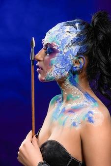Um rosto lateral de uma jovem garota bonita com uma maquiagem fantástica e brilhante, feita por um artista nas cores azul, branco e violeta. a garota segura uma flecha perto do rosto.