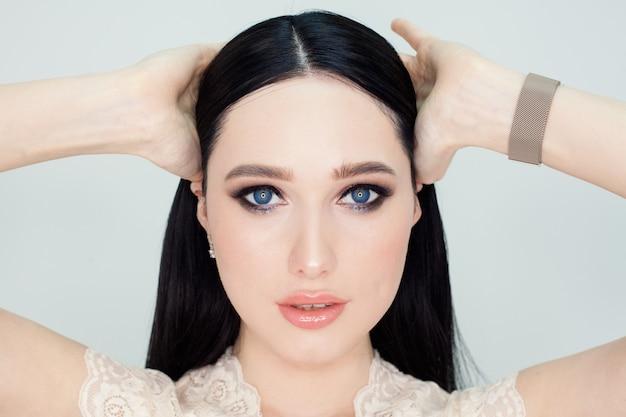 Um rosto limpo com a pele jovem, um retrato de uma mulher em uma parede branca. foto do conceito para a publicidade de produtos de limpeza facial e cremes com um efeito lifting.