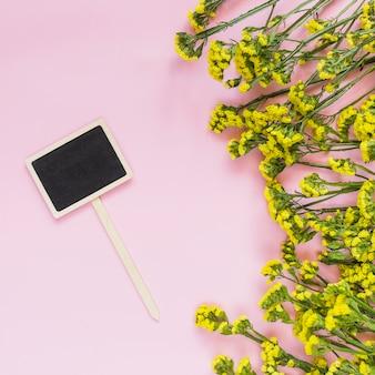 Um rótulo de lousa em branco e flores amarelas em pano de fundo rosa
