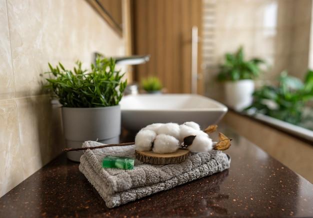 Um sabonete feito à mão e algodão branco repousa sobre uma toalha de algodão cinza em um banheiro moderno