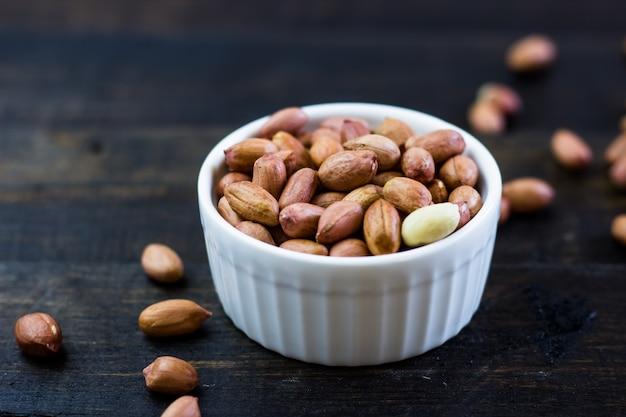 Um saboroso arranjo de nozes amendoins em uma tigela sobre uma mesa de madeira.