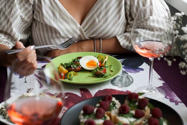 Um saboroso jantar para dois no restaurante: um prato de salada vegetariana fresca com ovo cozido, um prato de fatias de baguete perfumadas com rúcula e framboesa