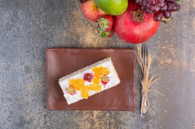 Um saboroso pedaço de bolo com várias frutas em espaço de mármore.