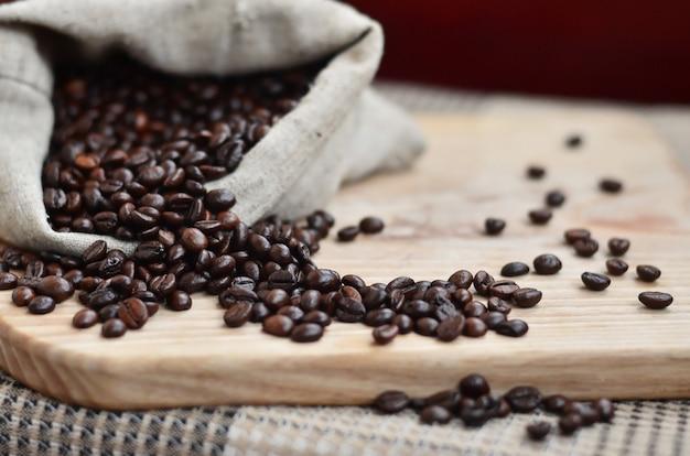 Um saco cheio de grãos de café marrons encontra-se em uma superfície de madeira