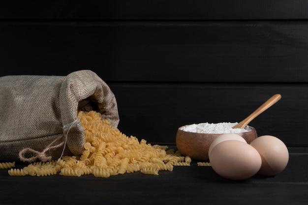 Um saco cheio de macarrão fusilli seco cru com farinha e ovos de galinha. foto de alta qualidade