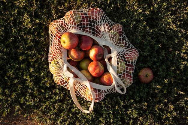 Um saco de barbante com maçãs vermelhas frescas encontra-se na grama. colheita de outono.