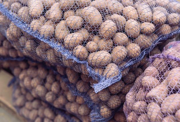 Um saco de batatas cruas e sujas. close-up de batatas frescas em uma grade.