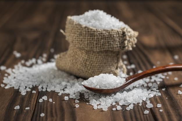 Um saco de sal e uma colher de pau em uma mesa rústica. sal marinho em pedra.