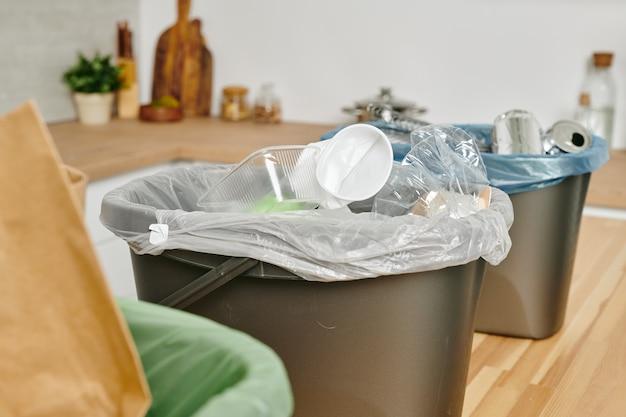 Um saco plástico com utensílios de cozinha descartáveis usados e outros resíduos na lata de lixo na mesa de madeira