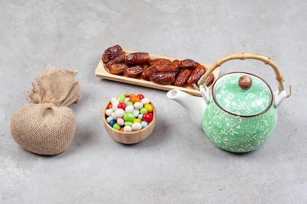 Um saco, uma tigela de doces, uma bandeja de madeira com tâmaras e um bule sobre superfície de mármore.