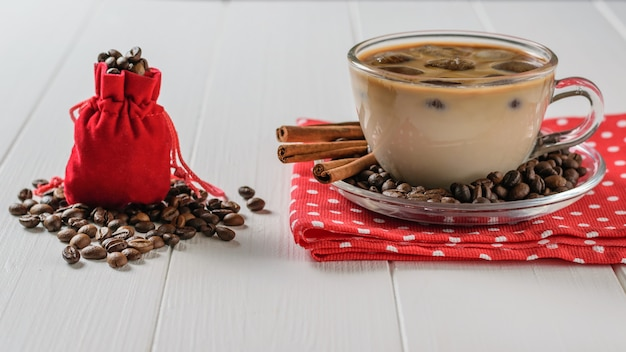Um saco vermelho encheu-se com os feijões de café e um copo do café e da canela de gelo em uma tabela branca.