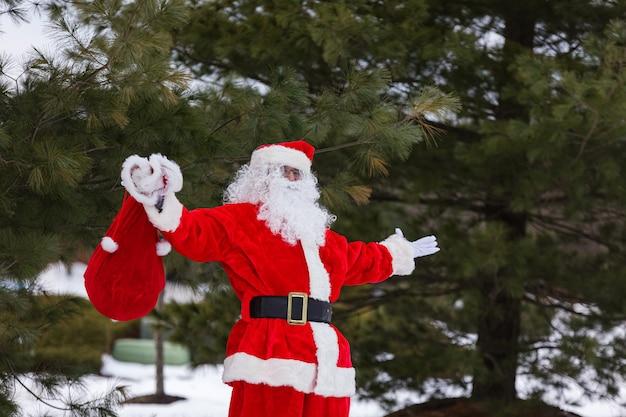 Um saco vermelho segurando presentes para as crianças no natal. papai noel em pé perto de uma árvore de natal em volta da neve branca