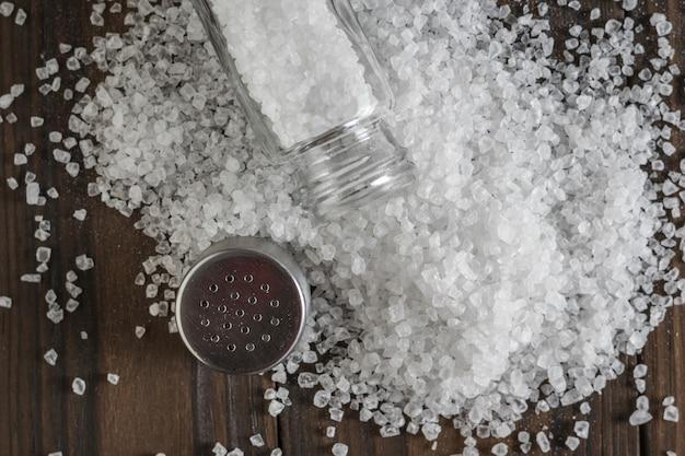 Um saleiro aberto em uma pilha de sal derramado sobre uma mesa de madeira. sal marinho em pedra.