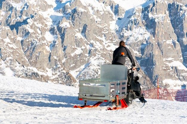 Um salva-vidas monta um snowmobile com um trenó ao longo da pista de esqui
