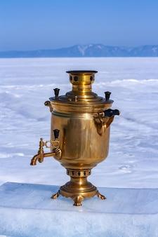 Um samovar fica em um pedaço de gelo em um fundo desfocado de um lago na neve e montanhas à distância. uma chaleira russa de cobre a lenha. hospitalidade russa. copie o espaço. vertical.