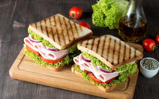 Um sanduíche com carne, salada, legumes