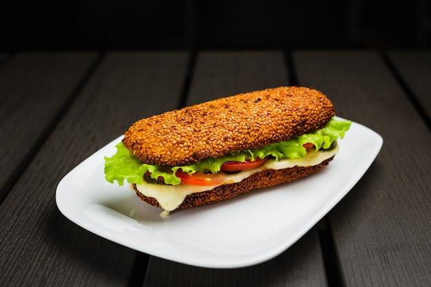 Um sanduíche com mussarela quente, tomate, alface e picles em um pão de gergelim