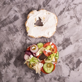 Um sanduíche vegetariano com legumes e queijo em um bagel