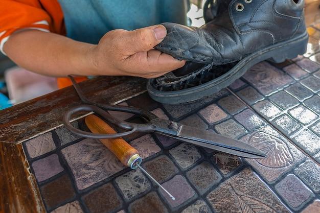 Um sapateiro consertando uma bota