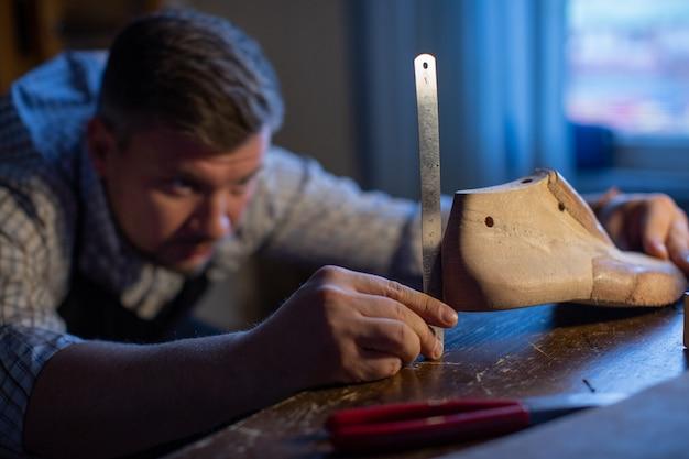 Um sapateiro profissional mede um bloco de sapatos de madeira com uma régua.