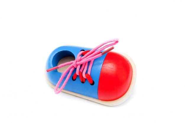 Um sapato de madeira compensada - brinquedo de desenvolvimento para as crianças aprenderem a amarrar cadarços isolados na superfície branca