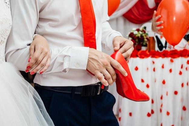 Um sapato de um pepino brega nas mãos do noivo