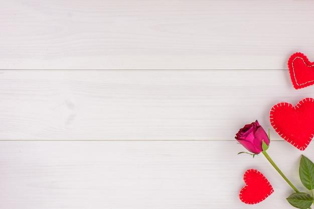 Um segmento de rosas vermelhas e corações em uma mesa de madeira branca. vista de cima, copie o espaço.