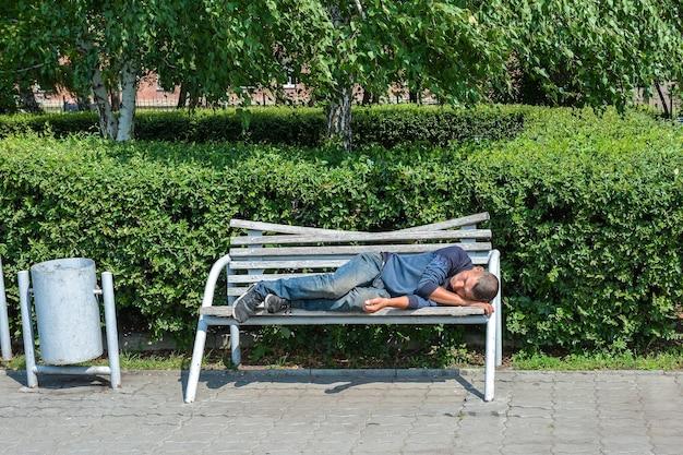 Um sem-teto dorme em um banco de um parque