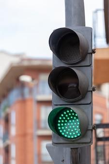 Um semáforo com três semáforos com o verde aceso permitindo a passagem de veículos