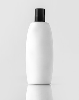 Um shampoo engarrafado branco vista frontal com tampa preta isolada na parede branca