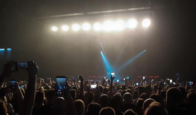Um show noturno de rock para um grande público em um clube filmando em telefones celulares
