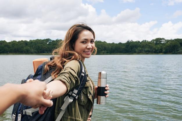 Um siga-me tiro com menina asiática, puxando a mão de seu namorado anônimo e sorrindo