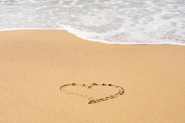 Um símbolo de coração escrito em uma praia de areia com espuma