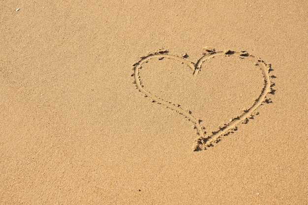 Um símbolo de coração escrito na areia