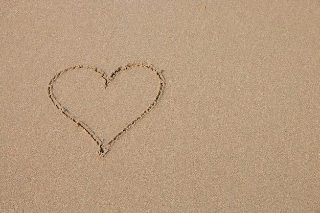 Um símbolo do coração na praia arenosa.