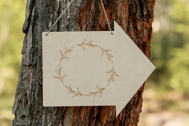 Um sinal anexado a uma árvore em forma de seta