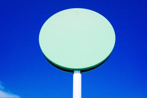 Um sinal circular em branco para incluir texto, com fundo de céu azul e espaço de cópia.