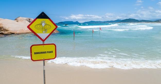 Um sinal de alerta indicando que não é permitido nadar devido às ondas grandes e perigosas do oceano. copie o espaço.