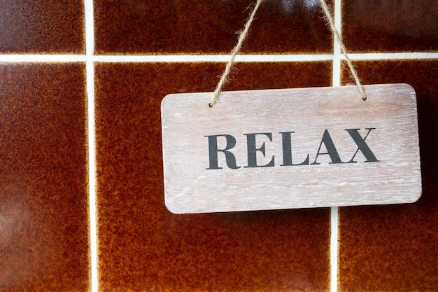 Um sinal de madeira relaxar em uma parede de azulejos marrom, textura de parede design retro