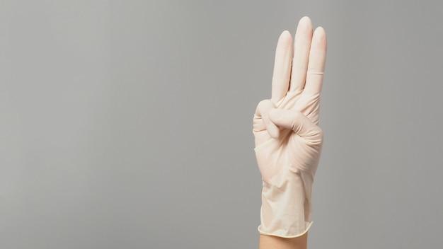 Um sinal de mão de 3 dedos aponta para cima, significando protesto ou três em fundo cinza. mão usa luva médica branca.