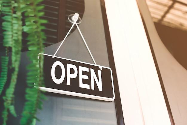 Um sinal de negócios que diz aberto no café ou restaurante está pendurado na porta na entrada. estilo de tom de cor vintage.