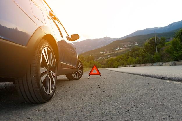 Um sinal de parada de emergência de um veículo é instalado na estrada, ao lado do carro. copie o espaço.