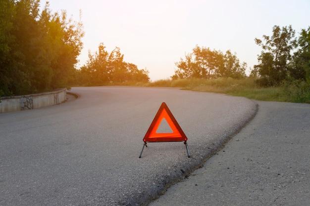 Um sinal de parada de emergência para um veículo está instalado na estrada. copie o espaço.