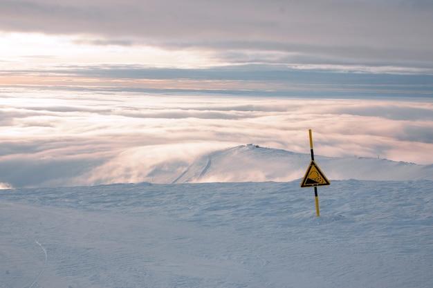Um sinal de perigo ou uma descida íngreme na pista de uma estação de esqui no inverno, uma paisagem com neve e nuvens no horizonte